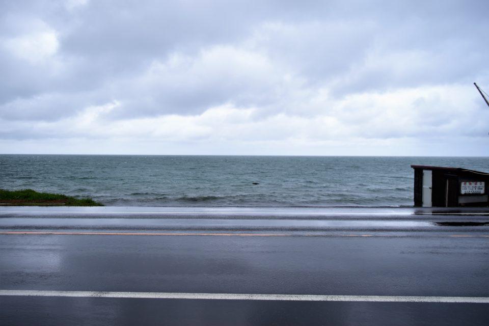 波しぶきと雨に濡れる道